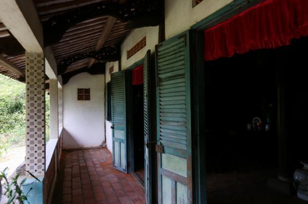 Hành lang, hiên và nền nhà được lát gạch Tàu, không gian rộng rãi hướng ra khu vườn rộng nên luôn mát mẻ. Cửa chính và các cửa sổ có song hình con tiện, bản gỗ.