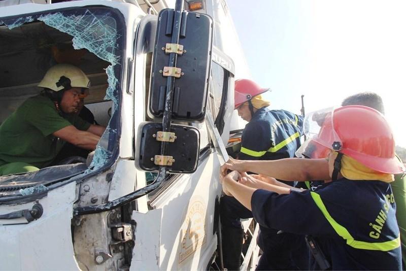 Lực lượng cứu hộ phải dùng máy cắt và hết sức nỗ lực để mở cửa cabin cứu người. Ảnh: HẢI HIẾU.