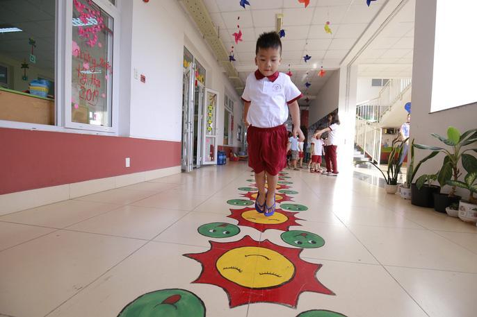 Nhân (4 tuổi) nhảy trong hành lang trường