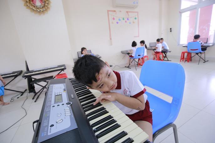 Đó là phòng dạy đàn. Vỹ lắng nghe những âm thanh xa lạ từ tiếng đàn phát ra