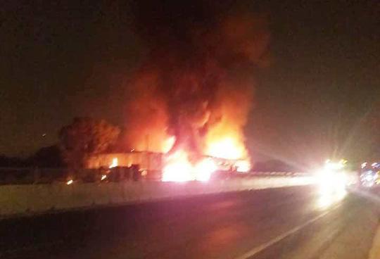 Chiếc xe khách bùng cháy dữ dội, bao gtrumf cả tiệm vá vỏ xe (Ảnh: Xuân Ánh)