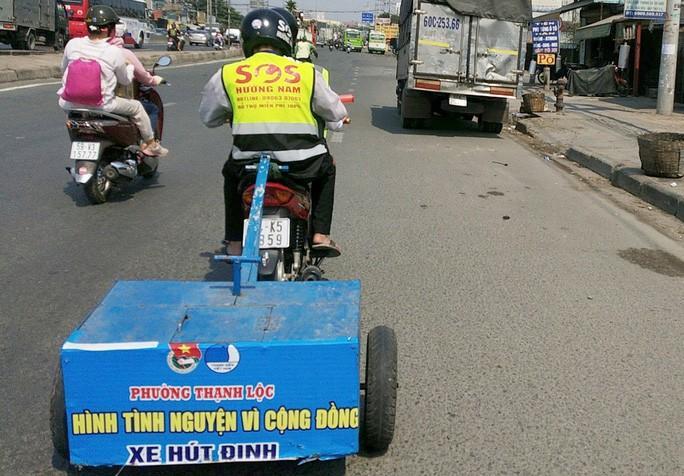 Thành viên nhóm SOS Hướng Nam hút đinh trên Quốc lộ 1, đoạn qua quận 12, TP HCM