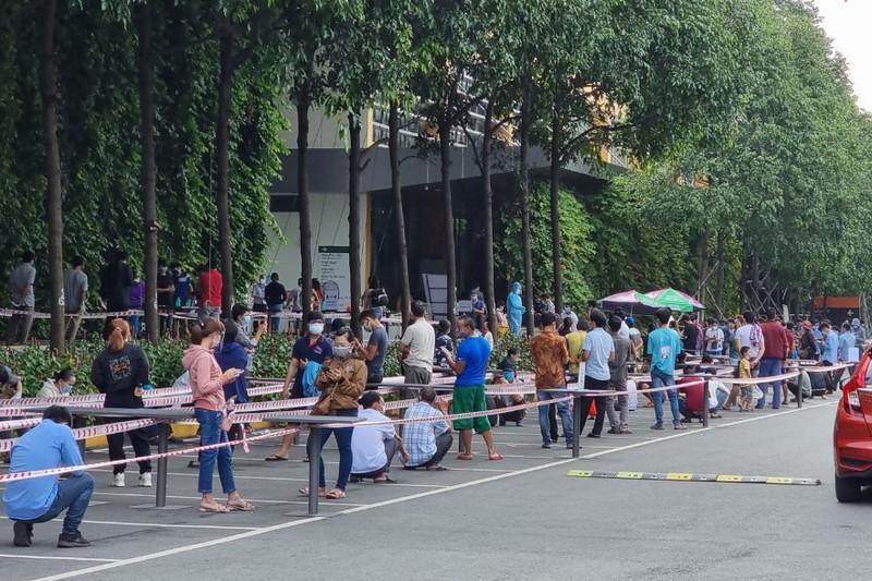 Người dân rồng rắn đứng giữa trưa nắng để chờ lấy mẫu test nhanh COVID-19 tại bệnh biện Quốc tế Becamex trong chiều 7-7. Ảnh: KD