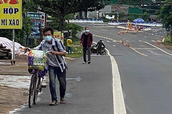 Anh em Chiến và Toản dắt xe đạp qua địa phận TP Gia Nghĩa, tỉnh Đăk Nông.