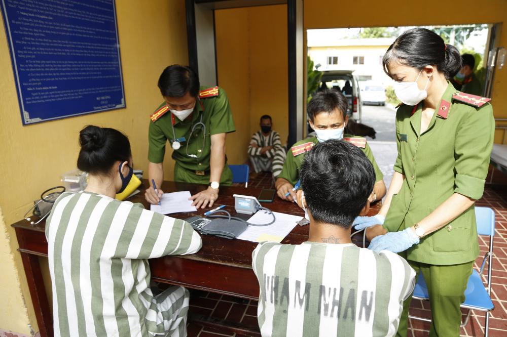 Các can phạm, phạm nhân được khám sàng lọc trước khi tiêm vắc-xin phòng Covid-19. (Ảnh Công an tỉnh Bình Dương).