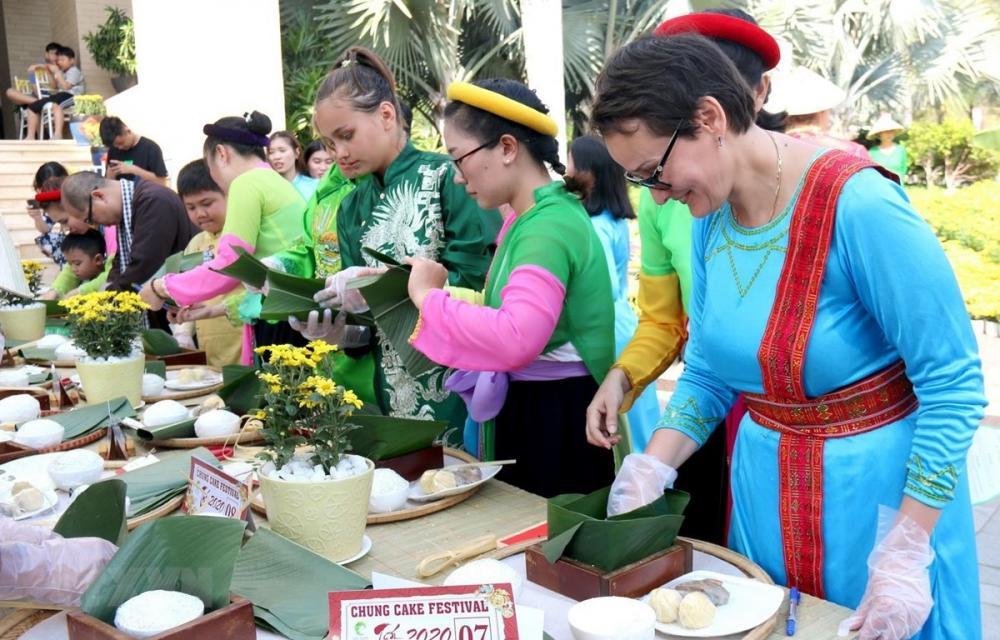 Du khách quốc tế hào hứng gói bánh chưng và trải nghiệm không gian Tết Việt (Ảnh: TTXVN)