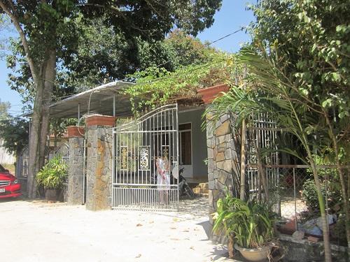 Khoảng sân phía trước rộng rãi của nhà Trường Giang ở quê. Cổng sắt có 3 cột ốp đá lớn.