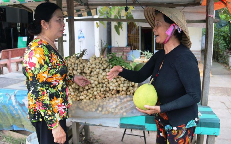 Cô Điệp (phải) người có thâm niên bán trái cây gần 20 năm ven lộ Vòng Cung, đoạn thuộc thị trấn Phong Điền. Ảnh: ĐĂNG HUỲNH
