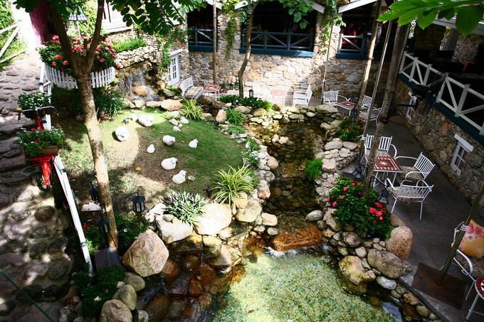 Khoảng sân trước hiên nhà đầy nắng gió, với cây xanh, thác nước và dòng suối nhỏ. Thiết kế sử dụng nhiều vật liệu tự nhiên gợi cảm giác mộc mạc, gần gũi.