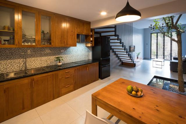 Không gian bếp và phòng khách được thiết kể mở, thoáng mát và được ngăn cách bằng một góc giếng trời có cây xanh và hồ cá.
