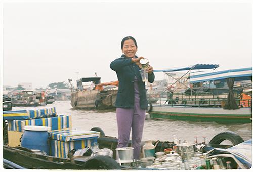 Không sợ sông nước xô đẩy, các chị vẫn có thể đứng và chế cà phê cho khách. Ảnh: Phong Vinh.