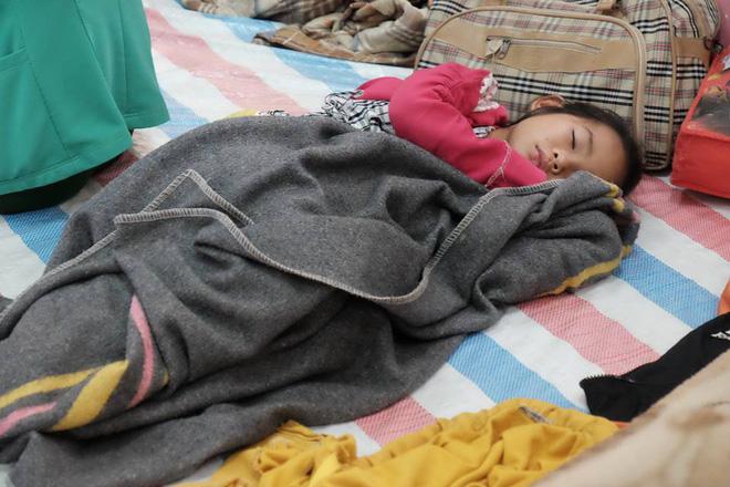 Một số trẻ em tranh thủ ngủ lấy sức tại điểm dã chiến