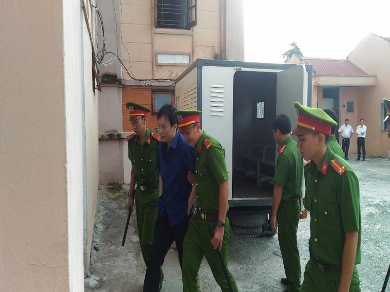Trong số 6 bị cáo thì chỉ còn mình bị cáo Nhân hiện đang bị tạm giam. Trong ảnh là bị cáo Nhân được cảnh sát Hỗ trợ tư pháp dẫn giải đến tòa sáng 18-4. Ảnh: NN