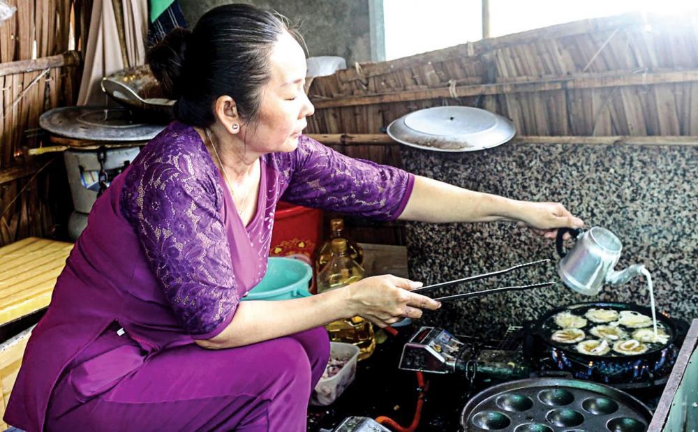 Chị Trần Thị Đặng đang làm món bánh khọt mực sữa. Ảnh: ÁI LAM