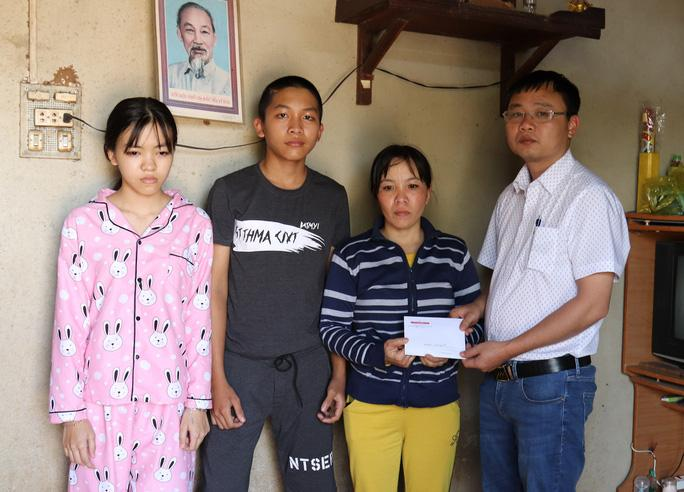 Phóng viên Báo Người Lao Động trao tiền bạn đọc ủng hộ gia đình chị Phượng. Ảnh B.N