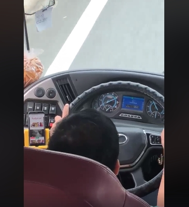 Tài xế vừa lái xe vừa liếc màn hình điện thoại. Ảnh cắt từ clip