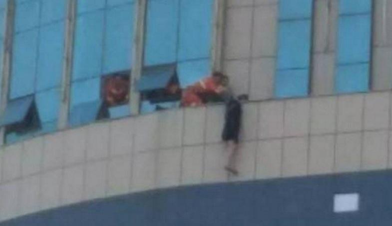 Lực lượng cứu hộ tiếp cận nạn nhân ngồi trên tầng 8 trung tâm thương mại. Ảnh: SCMP