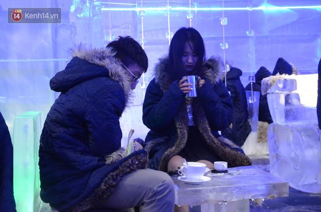 Đôi bạn trẻ vừa uống cà phê vừa co rúm vì lạnh.