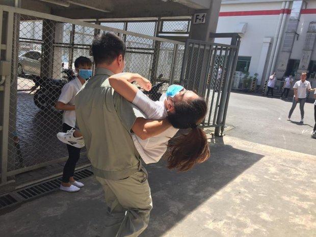 Hình ảnh nữ công nhân bị ngất xỉu được đưa ra ngoài.