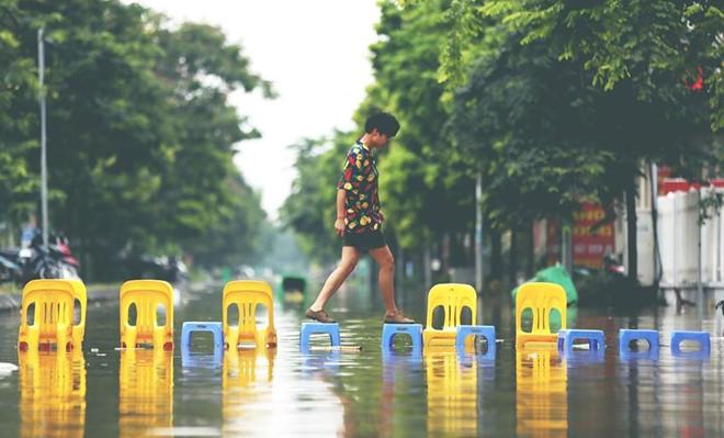 Nhân vật chính của bức ảnh là một phóng viên đang tìm hiểu tình hình ngập lụt ở các khu đô thị của Hà Nội.(Ảnh: Nam Nguyễn)