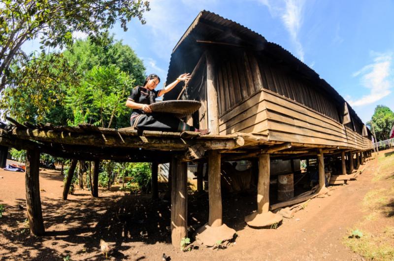 Hình ảnh có thể bạn bất chợt gặp trong buôn làng: cô gái dân tộc Ê Đê ngồi ray gạo trên nhà.