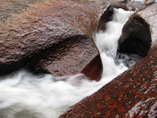 Nước mềm mại lướt trên những phiến đá đỏ hỏm ở thác Trâu Đá - Ảnh: Baodaklak.vn