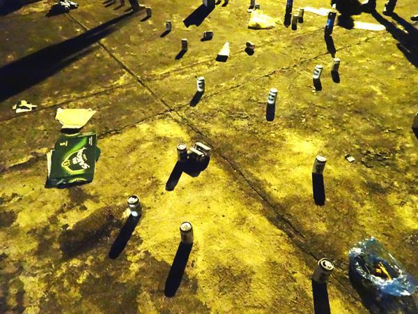 Những lon bia vứt bừa bộn được nhóm thanh niên mang đến khu vực nghĩa trang.