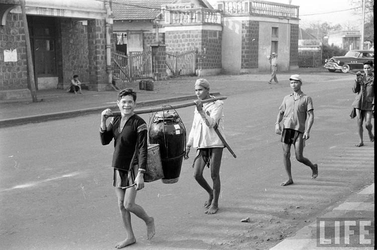Hai người đàn ông gánh một vò rượu cần trên đường phố Buôn Ma Thuột. Ảnh: Life