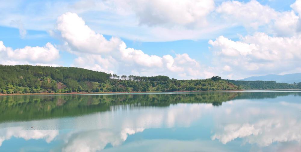 Mây và hàng cây soi bóng xuống mặt hồ.