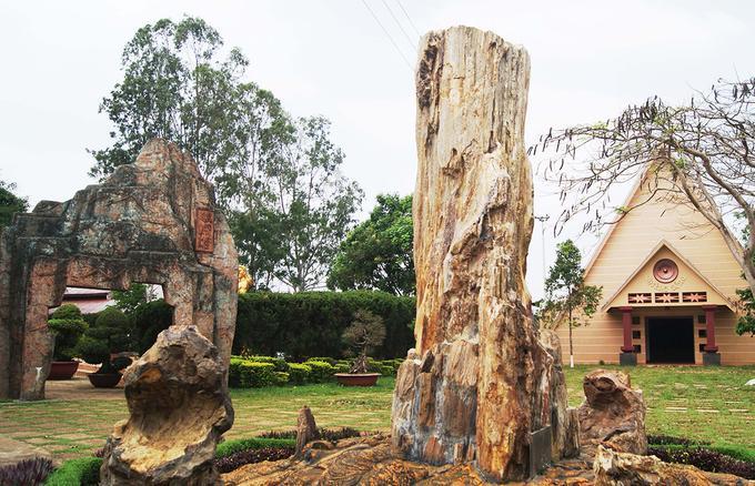 Thân gỗ hóa thạch lớn như chiếc linga đặt bên cạnh mái nhà rông, biểu tượng văn hóa Tây Nguyên tại Công viên Đồng Xanh, xã An Phú, thành phố Pleiku, tỉnh Gia Lai.