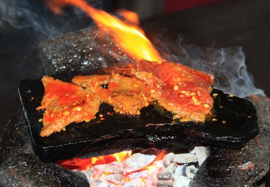 Một miếng đá mỏng được nun nóng, thịt bò được nhúng qua dầu và nướng chín trên phiến đá.