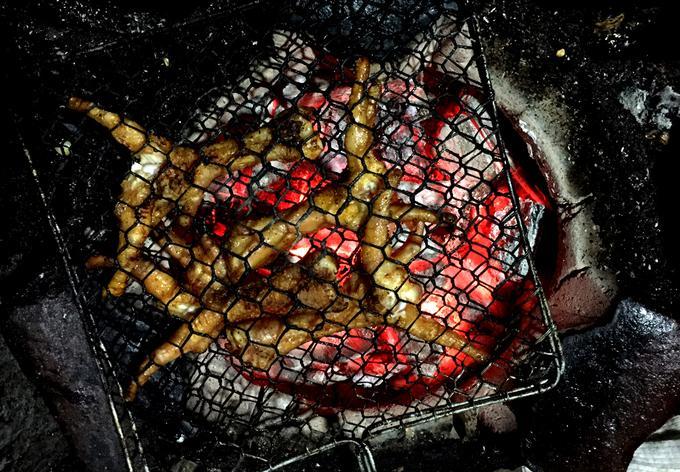 Chân gà sẽ được nướng đến khi cháy vàng trên lửa than, nhưng trước đó chủ quán đã tẩm ướp và nướng qua. Khi khách đến gọi, chân gà được kẹp vào vỉ kim loại và nướng trên bếp than hồng.