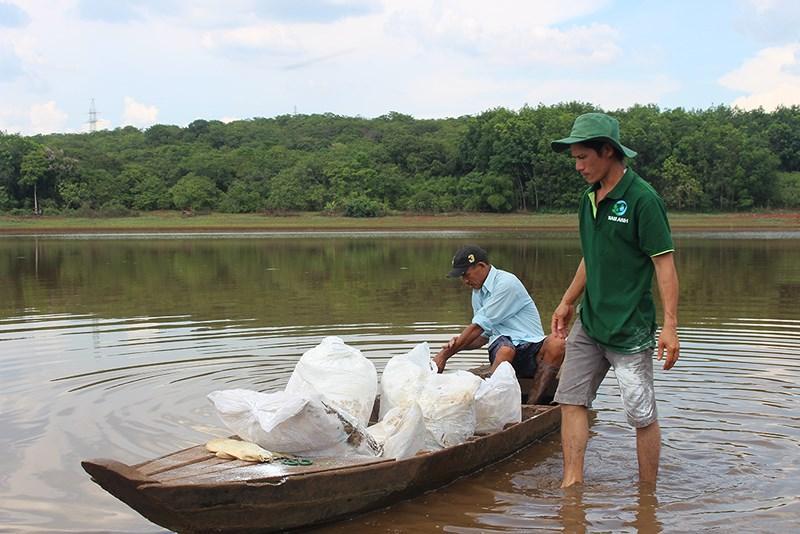 Gia đình người dân vùng hồ Bình Hà đang rắc vôi vệ sinh vùng hồ đập