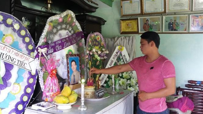 Trần Văn Truyền thắp nhang trên bàn thờ cha