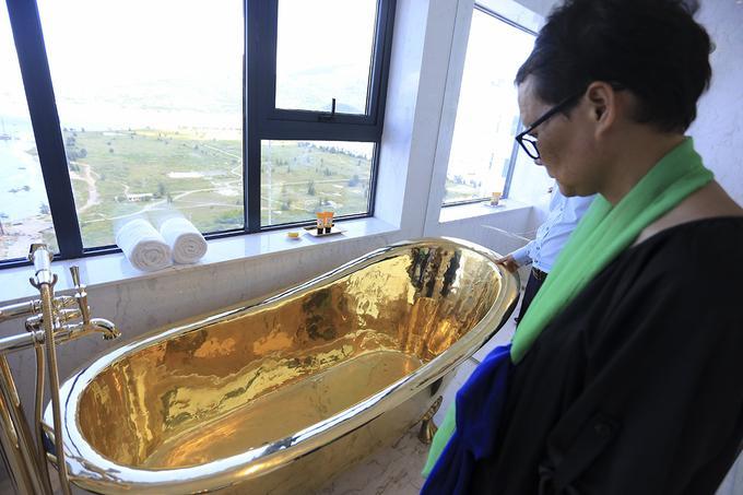 Bồn tắm mạ vàng được đặt cạnh sửa sổ nhiều ánh sáng.