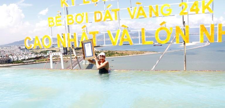 Cười tươi bên tấm bằng xác lập kỷ lục Việt Nam và Thế giới về bể bơi dát vàng cao và lớn nhất thế giới.
