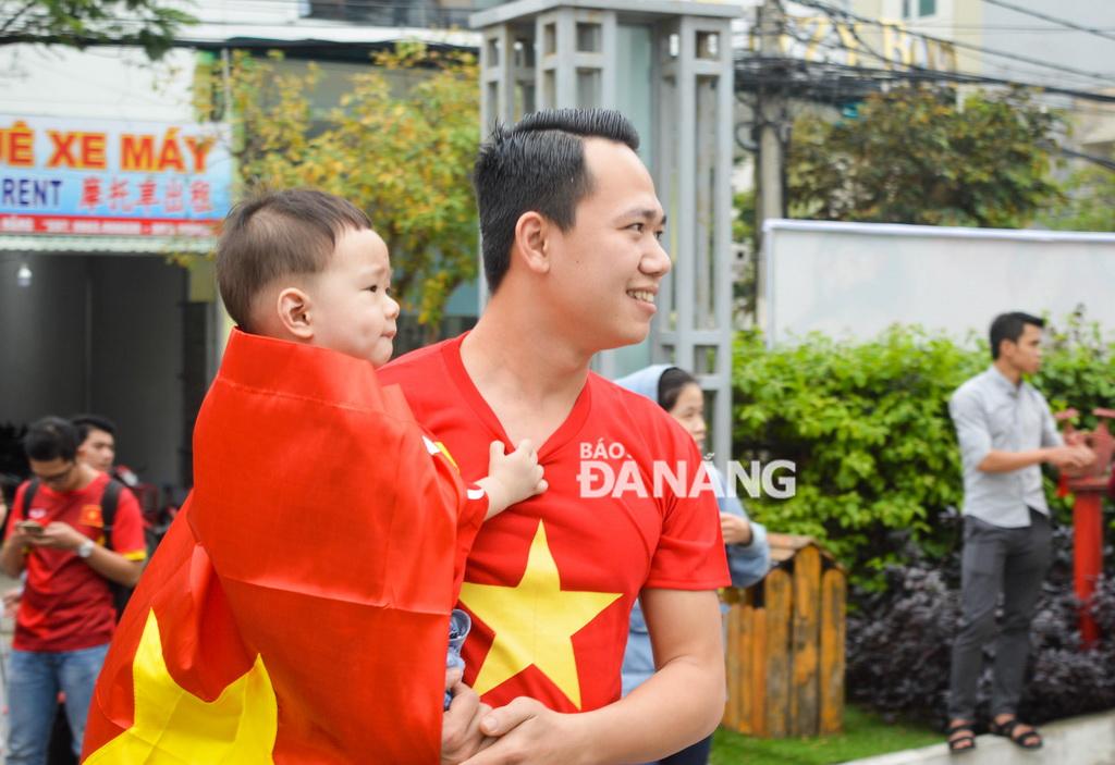 Một ông bố đưa con đi cổ vũ đội tuyển tại khuôn viên khách sạn Royal Lotus (quận Sơn Trà).