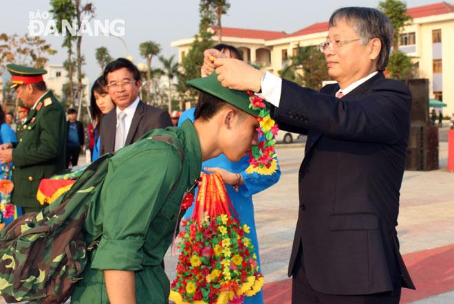 Phó Chủ tịch UBND thành phố Nguyễn Ngọc Tuấn trao hoa chúc mừng các tân binh tại điểm giao quân quận Liên Chiểu. Ảnh HUỲNH TRANG