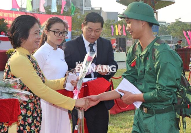 Chủ tịch Ủy ban MTTQ Việt Nam thành phố Đặng Thị Kim Liên tặng hoa chúc mừng các tân binh tại điểm giao quân quận Thanh Khê. Ảnh: NGỌC HÀ