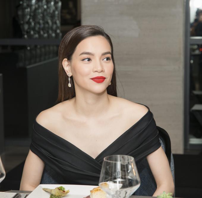 Hồ Ngọc Hà mặc bộ đầm đen trễ vai và tô son rực rỡ, trông vừa quyến rũ, vừa kiêu sa. Gần đây cô lấn sân kinh doanh son môi và đạt được thành công bước đầu.
