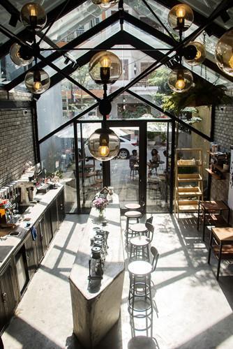 Mái kính cho ánh nắng ngập tràn không gian quán cà phê.