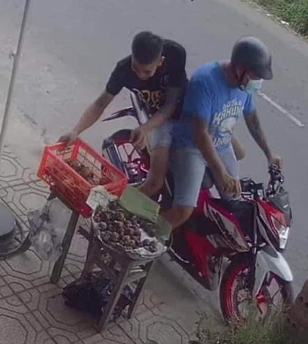 Hai thanh niên dừng xe lại rồi bê luôn rổ măng cụt bên vệ đường.