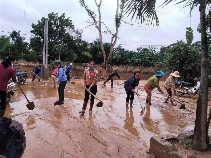 Người dân huyện Cam Lộ dọn bùn, vệ sinh môi trường ngay sau khi nước rút. Ảnh: VGP Thế Phong