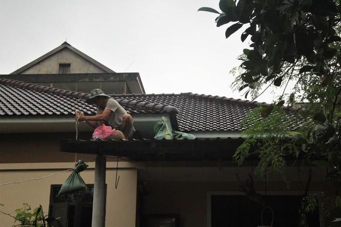 Người dân TP Đông Hà (Quảng Trị) dùng bao cát đằn lên mái nhà chống bão số 13
