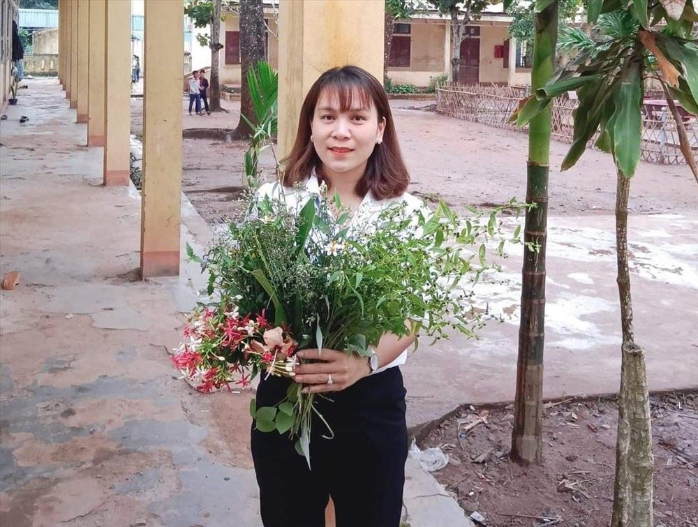 Nữ giáo viên Hoàng Thị Kim Chung - Trường Tiểu học và Trung học cơ sở A Xing bên bó hoa dại của học sinh tặng ngày 20.11. Ảnh: GV.