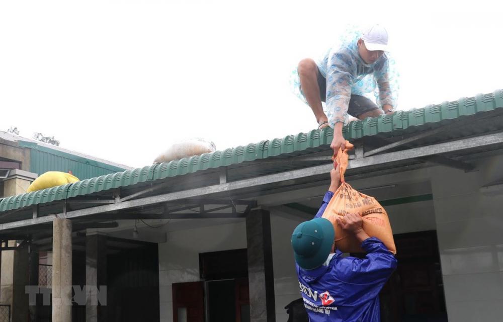 Người dân xã Gio Mai, huyện Gio Linh, tỉnh Quảng Trị đưa bao tải đựng cát lên gia cố mái nhà phòng chống bão số 13. (Ảnh: Nguyên Lý/TTXVN)