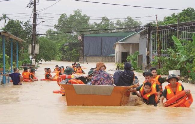Lực lượng chức năng tỉnh Quảng Trị hỗ trợ di dời người dân đến nơi an toàn trong mưa lũ.