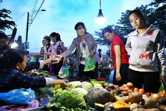 Công nhân Khu công nghiệp Tân Tạo, quận Bình Tân mua đồ ăn sau khi tan ca. Ảnh: Hữu Khoa.