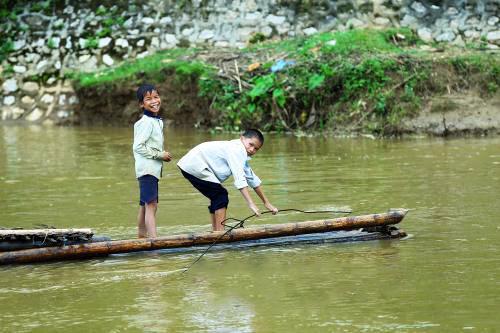 Trẻ em cũng qua suối bằng bè mảng và vô tư không nhận thức được nguy hiểm