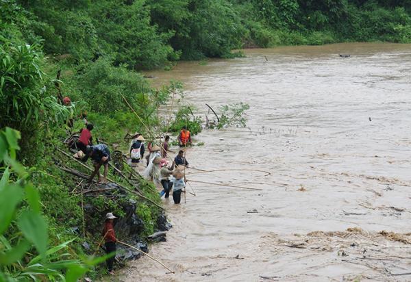 Người dân xã Mường Pồn, huyện Điện Biên bất chấp lũ dữ vẫn liều mình vớt củi trên suối Nậm Mức, đoạn qua xã Mường Pồn.